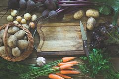 Fresh vegetables from carrot, beetroot, onion, garlic, potato on old board. Top view. Fall. Copy space on cutting board. Stock Photos