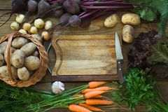 Fresh vegetables from carrot, beetroot, onion, potato on old wooden board. Top view. Copy space on cutting board. Royalty Free Stock Image