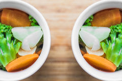 Fresh vegetables: carrots, broccoli, onions, potatoes. Two white cups with fresh vegetables: bright green broccoli, rich orange carrots, white onions, potatoes Stock Photo