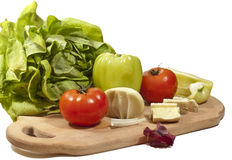 Fresh vegetables with cheese. On the chopping board isolated on white background Stock Photos