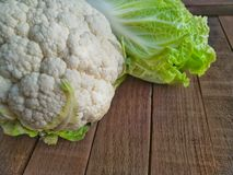 Fresh vegetables chinese cabbage and cauliflower close-up. Fresh vegetables chinese cabbage and cauliflower close-up on a rustic wooden background. The concept royalty free stock images
