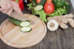Fresh vegetables on chopping board and dark table. Zucchini cut into pieces, over a wooden table made a composition of vegetables Stock Photos