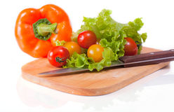 Fresh vegetables on a chopping board and knife. Fresh paprika, tomatoes and lettuce on the kitchen blackboard. White background and reflection Stock Images