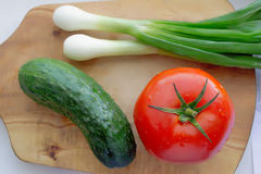 Fresh vegetables close up. Fresh vegetables tomato, onions, a cucumber on a chopping board royalty free stock image