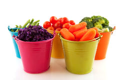 Fresh vegetables in colorful buckets stock photography