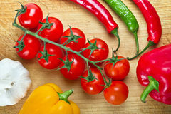 Fresh vegetables for cooking on cuting board. Tomatoes, chilli, garlic and peppers for cooking on cutting board with knife Stock Photography