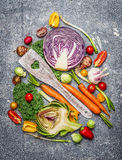 Fresh vegetables with cooking spoon composing on rustic background, top view. Stock Photos