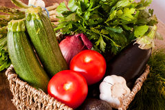 Fresh vegetables on countryside wooden tabletop. Including tomatoes, onions, avocados, asparagus, garlic, aubergines and courgettes Stock Photos