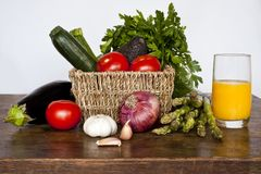 Fresh vegetables on countryside wooden tabletop. Including tomatoes, onions, avocados, asparagus, garlic, aubergines and courgettes. Glass of orange juice on Stock Image