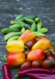 Cucumbers, tomatoes, peppers, on a wooden table stock image
