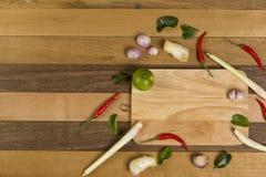 Fresh vegetables on cutting board, chili, lemon grass, lemon leaf set on wooden background royalty free stock photo