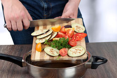 Fresh vegetables on the cutting board are falling in the pan. Concept of cooking. Royalty Free Stock Photos