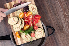 Fresh vegetables on the cutting board are falling in the pan. Concept of cooking. Royalty Free Stock Photo