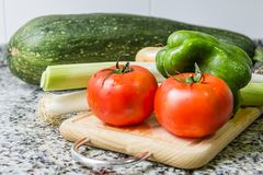 Fresh vegetables on cutting board in the kitchen Royalty Free Stock Photos