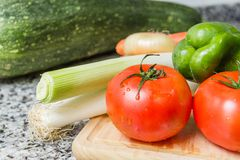 Fresh vegetables on cutting board in the kitchen royalty free stock image