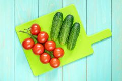 Fresh vegetables on cutting board. Fresh tomatoes and cucumbers on cutting board Stock Images