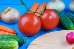 Fresh vegetables and cutting board on wooden table. Fresh vegetables and cutting board on blue wooden table Stock Photography