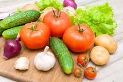 Fresh vegetables on a cutting board on a wooden table close up. Horizontal photo Royalty Free Stock Images