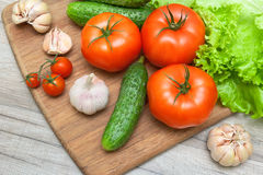 Fresh vegetables on a cutting board on a wooden table. Horizontal photo Royalty Free Stock Image