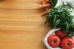 Fresh vegetables in eco cotton bags on wooden table in kitchen. Carrots,tomatoes, arugula from market in canvas reusable bags. Zero waste grocery shopping stock photo