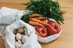 Fresh vegetables in eco cotton bags on wooden table in kitchen. Carrots,tomatoes, arugula, mushrooms from market in canvas. Reusable bags. Zero waste grocery stock photography