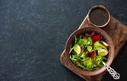 Fresh vegetables and eggs salad. Served in a clay pot over black stone background.  Top view. Copy space Royalty Free Stock Images