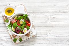 Fresh vegetables and eggs salad. Served in a clay pot over white wood background.  Top view. Copy space Royalty Free Stock Photos