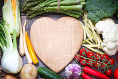Fresh vegetables and empty heart shaped cutting board Stock Image