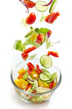 Fresh vegetables falling into the glass bowl Royalty Free Stock Photo