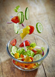 Fresh vegetables falling into the glass bowl Royalty Free Stock Photos