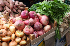 Fresh Vegetables At A Fruit Market. Fresh Sweet Potatos, Salad Leaves and red and yellow onions at A Fruit Market Royalty Free Stock Photo