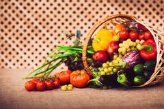 Fresh vegetables, fruits and lettuce in wicker basket. On kitchen table, covered Sack cloth on a background of a wooden lattice. Healthy life concept. Warm royalty free stock images