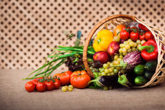 Fresh vegetables, fruits and lettuce in wicker basket. On kitchen table, covered Sack cloth on a background of a wooden lattice, copy space at left. Healthy stock images