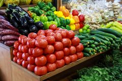 Fresh vegetables in the greek grocery shop. Fresh vegetables tomatoes, cucumbers, peppers, eggplants, ginger, greens on the counter in the greek grocery shop stock images