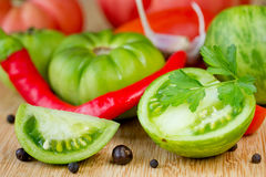 Fresh vegetables - green tomatoes, red hot chili pepper, garlic,. Parsley and spices closeup Royalty Free Stock Images