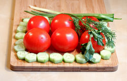 Fresh vegetables and greens. On the chopping board Stock Image