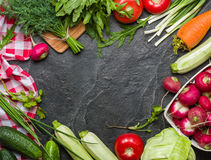 Fresh vegetables and greens in bunches arranged in a frame on a black stone background. Stock Image