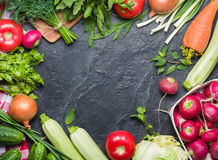 Fresh vegetables and greens in bunches arranged in a frame on a black stone background. Stock Images