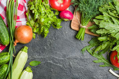 Fresh vegetables and greens in bunches arranged in a frame on a black stone background. Royalty Free Stock Photos