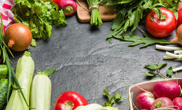 Fresh vegetables and greens in bunches arranged in a frame on a black stone background. Royalty Free Stock Image
