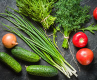 Fresh vegetables and greens in bunches arranged in a frame on a black stone background. Stock Photography