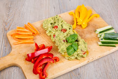 Fresh vegetables with guacamole. On wooden board Stock Image