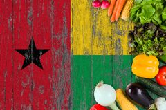 Fresh vegetables from Guinea Bissau on table. Cooking concept on wooden flag background.  stock photos