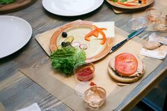 Fresh vegetables, hamburger bun and utensils for cooking classes on wooden table, concept of cooking class.  royalty free stock images