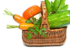 Fresh vegetables and herbs in a basket closeup on a white backgr Stock Images