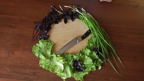 Fresh vegetables and herbs lie around a round cutting Board with knife on table. Fresh vegetables, green onions, Basil and lettuce lie around a round cutting stock footage