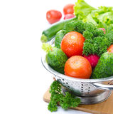 Fresh vegetables and herbs in metal colander, isolated. On a white background Stock Image