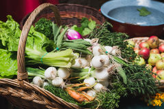 Fresh vegetables and herbs in rustic basket at Stock Image