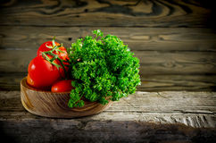Fresh vegetables and herbs, tomatoes and parsley on a wooden tab Royalty Free Stock Image