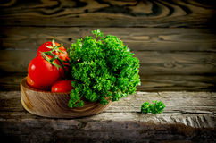 Fresh vegetables and herbs, tomatoes and parsley on a wooden tab Stock Image
